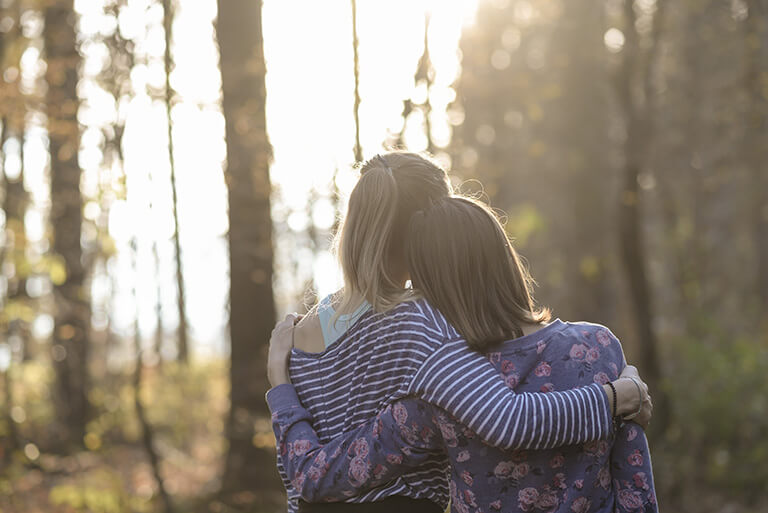 girls hugging in forest