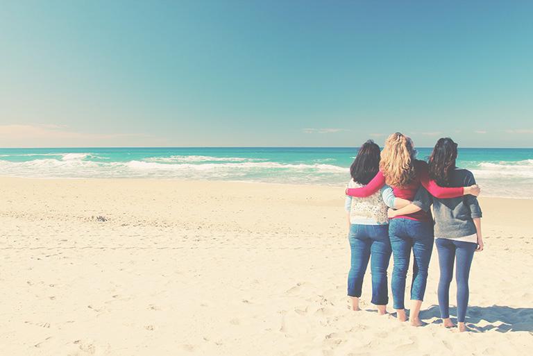 three women on beach having fun